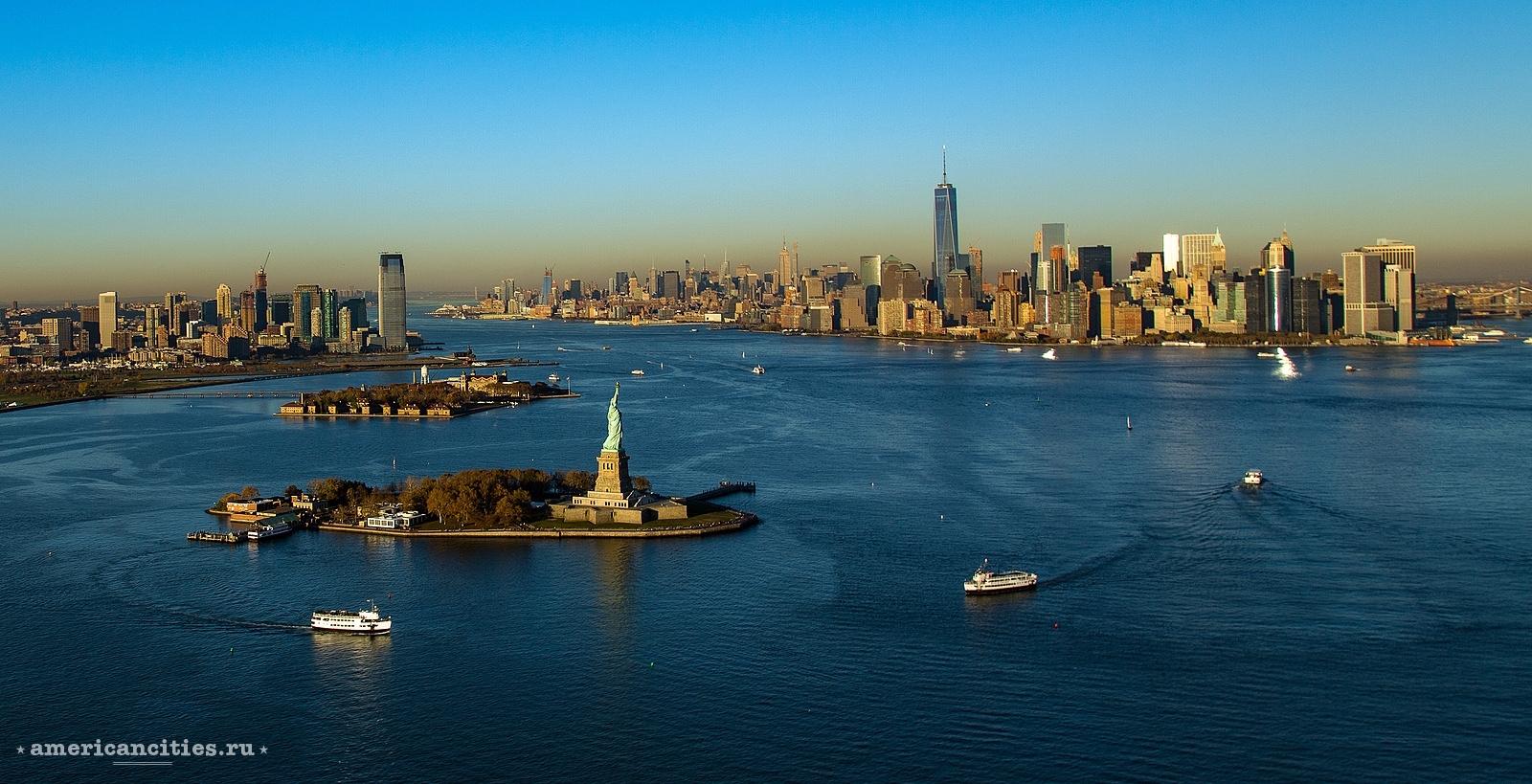 Джерси-Сити (слева) и Манхэттен (справа). На переднем плане Статуя Свободы на острове Либерти Айленд и остров Эллис Айленд